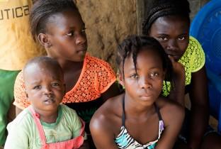 Pascaline (14 jaar, met oranje T-shirt), Noami (12 jaar, met groen T-shirt), Yonger (11 jaar) en Blessing (2 jaar) zitten voor hun huis. Na de dood van hun ouders zaten ze in quarantaine, maar nu mogen ze eindelijk weer naar buiten.