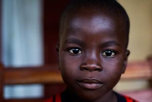 John, 5 jaar, verloor zijn twee ouders. Toen ze stierven had hij niemand om voor hem en zijn zus te zorgen.