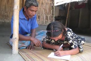 Rukhsana's vader uit Bangladesh helpt bij haar huiswerk. Hij vindt school voor z'n dochter net zo belangrijk als voor z'n zoon.