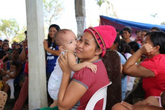 Plan International has started distributing relief items such as water and hygiene kits for 750 families affected by Typhoon Melor in Northern Samar. This mother and her baby are waiting for distributions from Plan International.