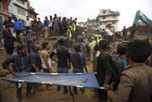 Rescue workers search for bodies as a stretcher is kept ready after an earthquake hit, in Kathmandu