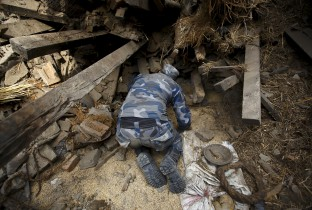 Rescue team member works to dig out the trapped body of a woman from a collapsed house a day after an earthquake in Bhaktapur