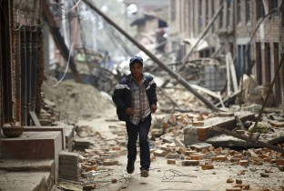 Man runs past damaged houses as aftershocks of an earthquake are felt a day after the earthquake in Bhaktapur
