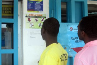 Youths reading public health information poster on Ebola in Voin